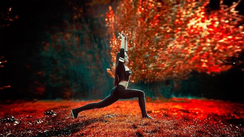 紅葉でホットヨガを楽しむ女性